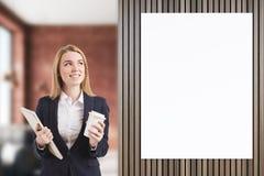 Lächelndes Bondmädchen nahe Plakat in einem Café Lizenzfreie Stockfotos