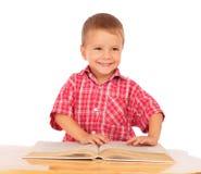 Lächelndes Buch des kleinen Jungen Leseauf dem Schreibtisch Lizenzfreie Stockfotos