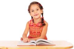 Lächelndes Buch des kleinen Mädchens Leseauf dem Schreibtisch Lizenzfreies Stockfoto