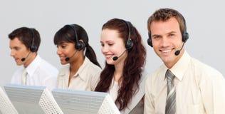 Lächelndes businessteam, das in einem Kundenkontaktcenter arbeitet