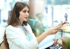 Lächelndes Call-Center-Vertreter, das auf etwas auf Bildschirm im hellen Büro zeigt stockfoto