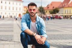 Lächelndes casualman mit Sonnenbrille knit draußen auf der Straße Lizenzfreies Stockbild