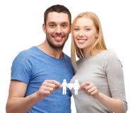 Lächelndes coule, das Papierfamilie mit Herzen hält Stockbilder