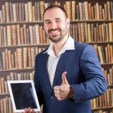 Lächelndes Darstellen des Geschäftsmannes auf Tablette in der Bibliothek Stockbild