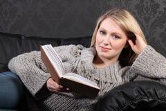 Lächelndes entspannendes Buch der blonden Frau Lesezu hause Lizenzfreie Stockfotografie