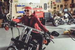 Lächelndes Fahren auf Motorrad im Mechanikershop stockfoto