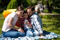 Lächelndes Familien-aufpassendes Foto am Handy beim Sitzen auf der Decke im Park lizenzfreies stockbild