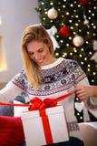 Lächelndes Frauenöffnung Weihnachtsgeschenk Stockfoto
