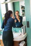 Lächelndes Frauenbadezimmer, das Lippenstiftspiegelgeschäftsfrau anwendet stockbilder