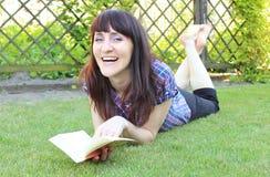 Lächelndes Frauenlesebuch auf dem Gras im Garten Stockfotografie