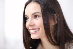 Lächelndes Frauenporträt beim Profilschauen, lokalisiert auf Weiß stockfotografie