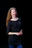 Lächelndes frohes junges Mädchen blinzelt ihr rechtes Auge auf einem schwarzen Hintergrund Stockbild