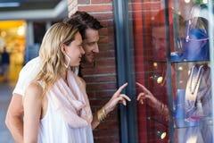 Lächelndes gehendes Fenstereinkaufen der Paare und Zeigen auf Halsketten Lizenzfreie Stockfotografie