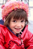 Lächelndes gekleidetes rotes Mädchen am Winter Stockfoto
