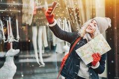 Lächelndes gelocktes blondes Mädchen mit der Karte, die selfie, Winter macht stockbilder