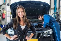 Lächelndes Geschäftsfrau-With Mechanic Repairing-Auto in der Garage Lizenzfreies Stockbild