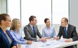 Lächelndes Geschäftsteam bei der Sitzung Stockfotos