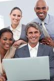 Lächelndes Geschäftsteam, das an einem Laptop arbeitet lizenzfreie stockfotos