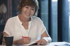 Lächelndes Gesicht, Bildung und Konzept zu Hause bearbeiten der Asiatin Lizenzfreies Stockfoto