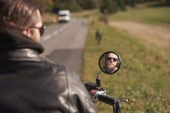 Lächelndes Gesicht des hübschen bärtigen glücklichen Radfahrers in der dunklen Sonnenbrille reflektierte sich im Motorradspiegel stockfotos