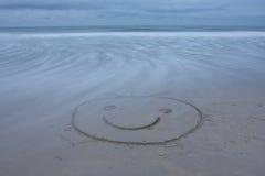 Lächelndes Gesicht zeichnete auf Strand stockfoto