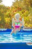 Lächelndes gesundes Mädchen, das im Swimmingpool sitzt Stockbilder