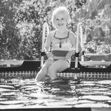 Lächelndes gesundes Mädchen, das im Swimmingpool sitzt Lizenzfreies Stockbild