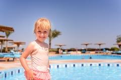Lächelndes glückliches kleines blondes Mädchen an einem Erholungsortpool Stockbilder