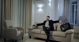 Lächelndes glückliches kommen des jungen Geschäftsmannes zu Hause nach der Arbeit sprang er auf das Sofa nimmt die Direktüber stock video