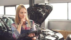 Lächelndes glückliches Mädchen, welches das Arbeiten an te Garage genießt stock footage