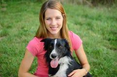 Lächelndes glückliches Mädchen, welches das rosa Hemd draußen umarmt mit ihrem weißen und schwarzen Hund im Park während des sonn Stockbild