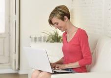 Lächelndes glückliches mit Laptop-Computer auf Sofacouch zu Hause arbeiten der jungen Schönheit Stockfoto