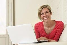Lächelndes glückliches mit Laptop-Computer auf Sofacouch zu Hause arbeiten der jungen Schönheit Lizenzfreie Stockfotografie