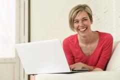Lächelndes glückliches mit Laptop-Computer auf Sofacouch zu Hause arbeiten der jungen Schönheit Lizenzfreies Stockbild