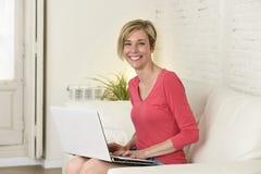 Lächelndes glückliches mit Laptop-Computer auf Sofacouch zu Hause arbeiten der jungen Schönheit Lizenzfreie Stockbilder
