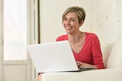 Lächelndes glückliches mit Laptop-Computer auf Sofacouch zu Hause arbeiten der jungen Schönheit Stockbilder