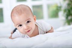 Lächelndes glückliches schönes Baby, das auf Bett liegt Stockfoto