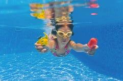 Lächelndes glückliches Unterwasserkind im Swimmingpool lizenzfreie stockfotos