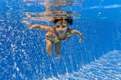 Lächelndes glückliches Unterwasserkind im Swimmingpool lizenzfreie stockbilder