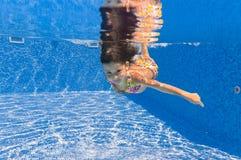 Lächelndes glückliches Unterwasserkind im Swimmingpool lizenzfreies stockfoto