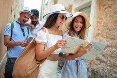 Lächelndes gorup von Freunden mit Karte Tourismus, Reise, Freizeit, Feiertage und Freundschaftskonzept lizenzfreies stockfoto
