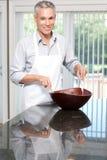 Lächelndes graues Haar bemannen werfenden Salat im Vorfeld Stockbild