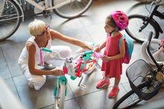 Lächelndes Großmutter- und Mädcheneinkaufsfahrrad und -sturzhelme im Fahrradgeschäft lizenzfreie stockfotografie