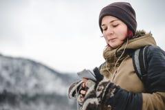 Lächelndes hörendes Mädchen die Musik in den Winterbergen Lizenzfreies Stockfoto