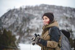 Lächelndes hörendes Mädchen die Musik in den Winterbergen Lizenzfreie Stockfotos