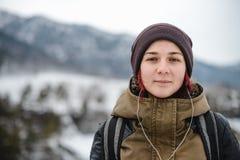 Lächelndes hörendes Mädchen die Musik in den Winterbergen Stockfoto