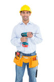 Lächelndes hübsches junges Heimwerkerholdingbohrgerät stockfotografie
