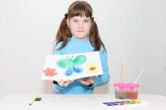 Lächelndes hübsches Mädchen zeigt Bild mit Schmetterling Lizenzfreie Stockfotografie