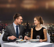 Lächelndes Hauptgericht Paaressens am Restaurant Stockbild