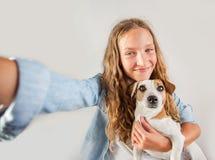 Lächelndes jugendlich Herstellungsselfie Foto auf Smartphone über nettem Mädchen des weißen Hintergrundes lizenzfreies stockbild